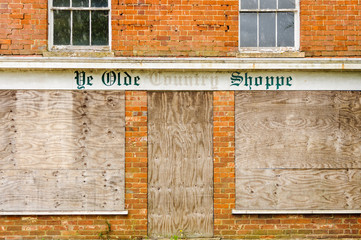 "Boarded up village shop with a sign saying ""Ye Olde Country Shoppe"""