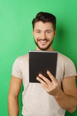 lachender mann mit tablet-pc vor grüner wand
