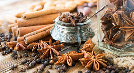 Aromatic spices on a rustic background. Clove, cinnamon in sticks, anise illicium, black peppercorns on old wooden table. Christmas and winter spices