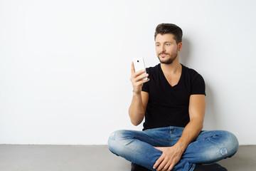 man sitzt auf dem boden in seiner wohnung und schaut auf sein mobiltelefon