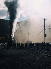 People standing on a railway as an old steam train travels down the tracks