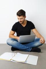 mann sitzt mit laptop und unterlagen auf dem fußboden