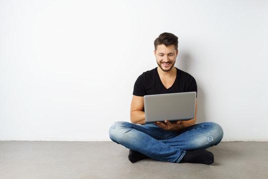 mann sitzt auf dem boden mit seinem laptop