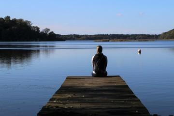 Frau sitzt an einem Steg am See