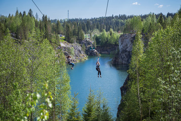 Tourist gliding on the zipline trip in the canyon Marble quarry in Ruskeala Park
