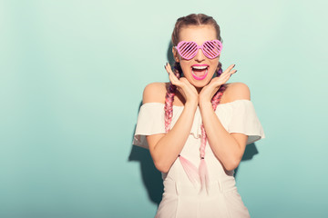 Excited woman with funny  heart glasses laughing. Studio shot on blue background.