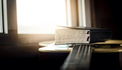 bible holy with acoustic guitar on wooden table