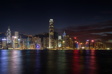 Hong Kong Island's skyline over Victoria Harbour with lit modern skyscrapers at night in Hong Kong, China. Viewed from Tsim Sha Tsui, Kowloon.