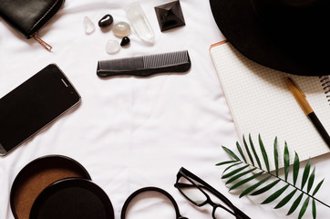 magnifier and glasses. clean notebook. hat, wallet, business card, phone
