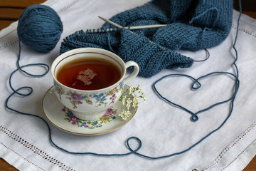 Still life with knitting  and cup of tea on the old doyley, heart made of yarn