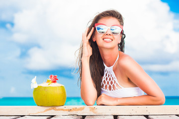 woman in bikini and sunglasses with fresh coconut cocktail relaxing on tropical beach