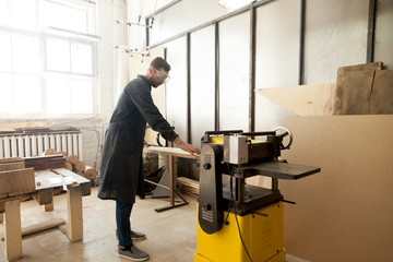 Young male carpenter using power tool for his work in small woodshop, working with stationary planer to reduce wooden boards thickness and smooth plank, cabinetmaker or joiner activity and woodworking