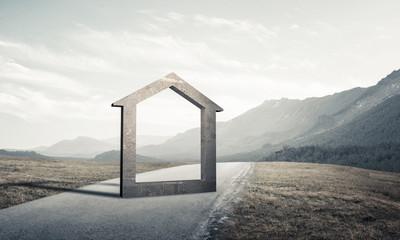 Conceptual background image of concrete home sign on asphalt roa