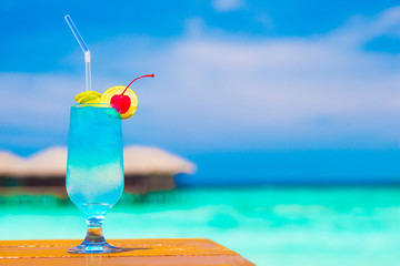 glass of blue curacao cocktail with cherry by the beach
