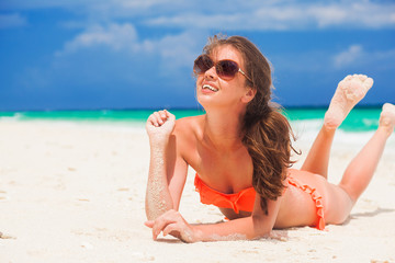 long haired woman in bikini relaxing at white sand beach
