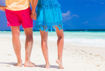 legs of young hugging couple on tropical turquoise beach