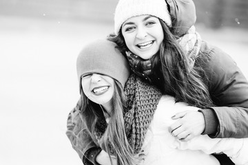 Girls in coats having fun on winter day. Best friends, happiness