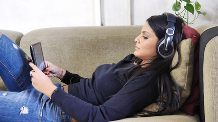 Pretty young woman watching video on tablet PC and using headphones, while lying on a couch at home in her living-room