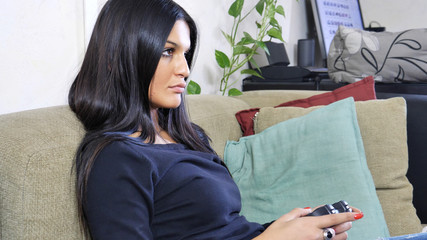 Good looking young woman holding joystick or gamepad, joypad, playing video game at home sitting on couch