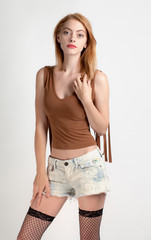 Thin, Attractive Woman in Crop Top, Jean Shorts, and Thigh High Fishnet Stockings