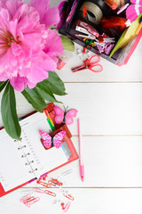 Planning concept for girl or woman with pink and red stationary over white wooden table