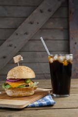Hamburger and cold drink on table