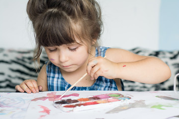 Cute kid is drawing. Beautiful little girl with paint brush and watercolor.