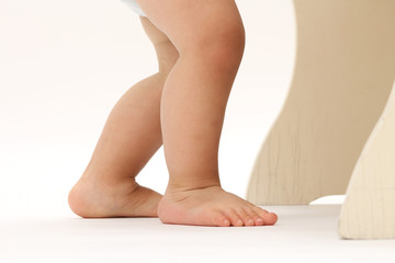 close-up on the legs and feet of a baby standing with his diaper