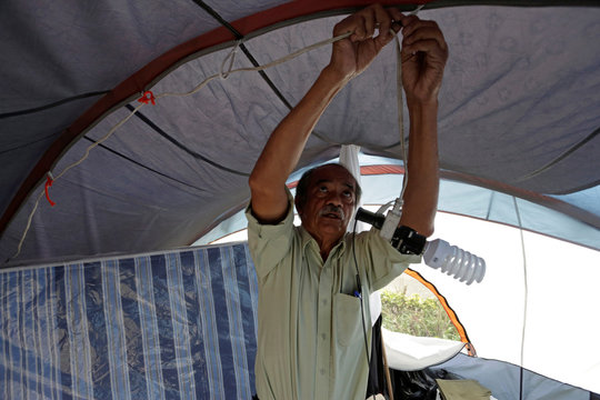 Miguel Gomez installs a light bulb inside a tent in a park and where he now lives with his family, after their home was destroyed in an earthquake, in Mexico City