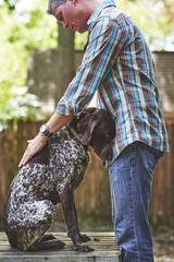 a man petting his sad dog