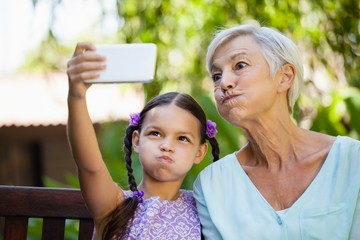 Girl and grandmother making faces while taking selfie