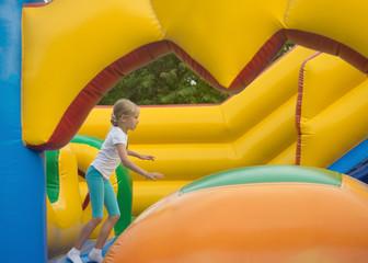Little girl fun fun on an inflatable trampoline.