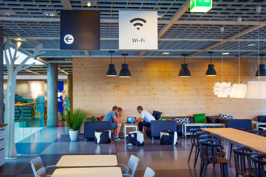 Wifi zone in modern cafe with blurred people on background. Wi-fi free at restaurant on blurred background.