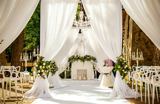 Place for wedding ceremony in white color ,with white fireplace and chandeliers decorated with flowers and white cloth and wooden chairs for guests on each side outdoors.