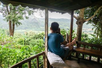 man takes photographs of hill top at resort