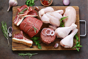 Poster Vlees raw meat assortment - beef, lamb, chicken on a wooden board