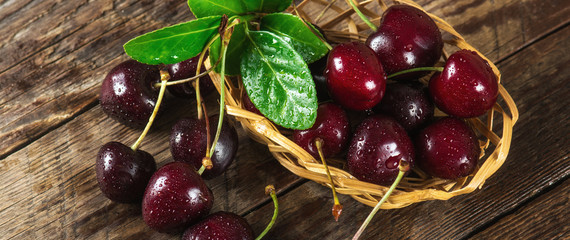 Cherry on a wooden table in a wicker