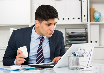 Young man is working at a computer and drinking coffee