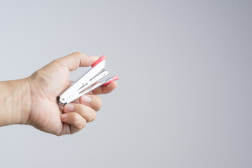 Hand holding stapler, an office supplies for  stapling pages of paper or similar material