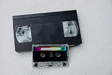 кассета аудио и чёрная видеокассета на сером столе