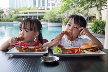 Asian Little Chinese Girls Eating Burger and Fried chicken