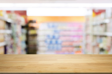 empty wooden desk in front of blurred montage hyper market background