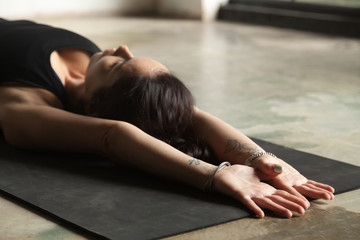 Young woman practicing yoga, stretching on mat, palms facing upward, relaxing after stressful situation in a restorative exercise, body and mind resting pose, indoor close up image, floor background
