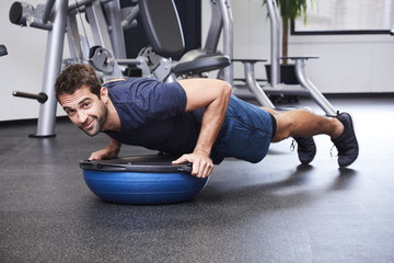 Dude performing press ups on bosu ball, portrait