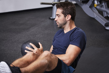 Exercise dude using medicine ball in gym