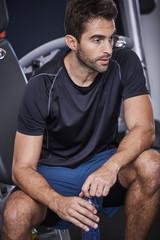 Sports guy taking a break in gym