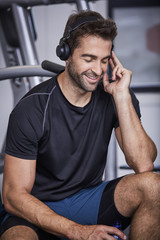 Gym guy lost in music with headphones in gym, smiling