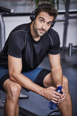 Gym dude with headphones and water, portrait
