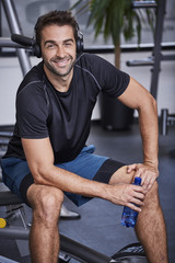 Smiling guy in gym with headphones and water bottle, portrait