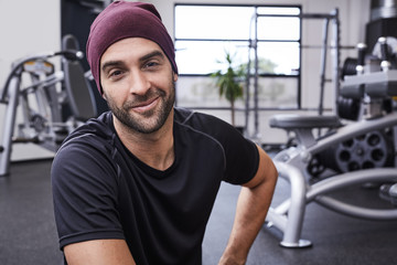 Smiling portrait of guy in gym wearing hat